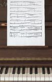Musical score and piano. A sheet of musical score on a piano detail Royalty Free Stock Photo