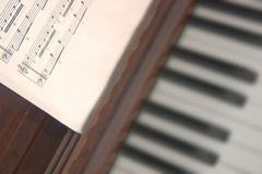 Musical score and piano. A sheet of musical score with a background blurred piano Stock Photo