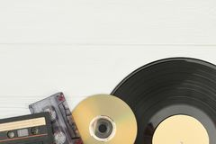 Musical storage devices and copy space. Old audio cassette tapes, compact disc and vinyl record on white wooden background with text space stock photo