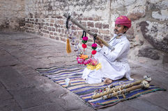 Musical Survival. A local musician playing rawanhatha - string instument, to entertain visiters in mehrangarh fort, jodhpur, rajasthan, india Royalty Free Stock Images