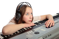 Musical synthesizer. Teen girl plays on a musical synthesizer and dreams royalty free stock image