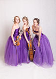Musical trio in purple dresses Stock Images