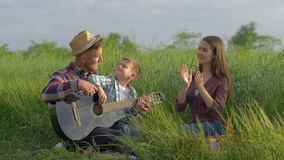 Musical upbringing, happy funny daddy teaches son to play guitar while claps and laughs while relaxing on family picnic. In nature in green grass close-up stock video footage