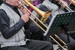 Musican viejo vestida en el chaleco clásico del ` s de los hombres que juega en un trombón en una orquesta, soporte de música det foto de archivo libre de regalías