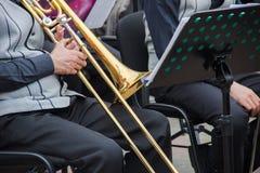 Musican viejo vestida en el men& x27; chaleco clásico que juega en un trombón en una orquesta, soporte de s de música detrás de é fotos de archivo