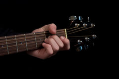 The Musician. The neck of an acoustic guitar with fingers placed on a chord Royalty Free Stock Photography