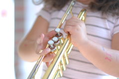 Musician. A six year old girl playing trumpet Stock Photos