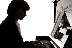 Musician. A silhouette of a girl playing the piano Stock Photography