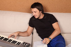 Musician. Composes music to the song with a synthesizer sitting on the sofa Stock Photos