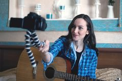 Musician with acoustic guitar on the bed records herself on DSLR camera keeping it in front of him on a gorillapod.  Royalty Free Stock Photos