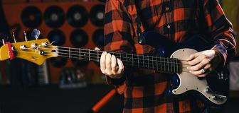 Musician, artist play electric guitar musical instrument. Male hands hold guitar, play music in club atmosphere. Background. Fingers clamp strings on guitar Royalty Free Stock Photography