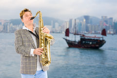 Musician in the background of Hong Kong. Royalty Free Stock Image