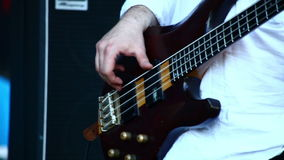 Musician bassist playing his bass guitar on a stage concert. Close up stock video footage