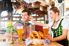 Musician in Bavarian Restaurant playing Accordion Stock Photo