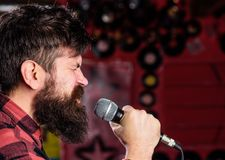 Musician with beard and mustache singing song in karaoke. Punk rock concept. Man with tense face holds microphone. Singing song, club background, side view royalty free stock images