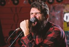 Musician with beard and mustache singing song in karaoke. Rock star concept. Man with tense face holds microphone stock photo