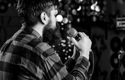 Musician with beard singing song in karaoke, rear view. Man in checkered shirt holds microphone, singing song, karaoke. Club background. Guy likes to sing in stock photography