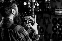 Musician with beard singing song in karaoke, rear view. Rock singer concept. Man in checkered shirt holds microphone. Singing song, karaoke club background stock image