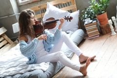 Musician in bed. Musician. Beautiful girl with violin royalty free stock photo