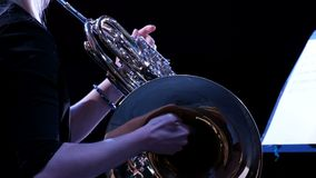 Girl blonde plays on the French horn. Close-up of female hands. Side view. Woman musician in an orchestra. Musician of a brass ban. Musician of a brass band stock footage