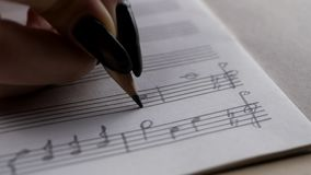 Musician or composer hand writes a song or a musical work. Writing notes with pencil on the pentagram stock video