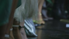 Unrecognizable people in costums dancing on the stage. The musician on the concert. View on the legs of singer at the stage. Performers of music dancing at the stock footage