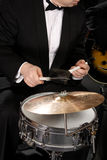 The musician with a drum and a plate. The musician plays a drum with a plate Royalty Free Stock Photography