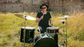 Musician drummer dressed in black clothes, hat, playing the drum set and cymbals stock video