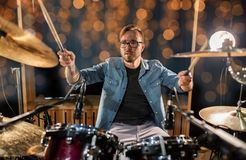 Musician or drummer playing drum kit at concert. Music, people, musical instruments and entertainment concept - male musician or drummer playing drums and Stock Photo
