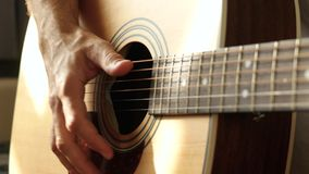 A musician extracts sound with his fingers from the strings of a yellow acoustic guitar, close-up. The concept of music and creativity. 4k stock video