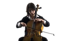Musician girl plays a violoncello rehearsing a composition. White background stock video footage