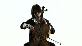 Musician girl plays a violoncello rehearsing a composition. White background. Slow motion stock video footage