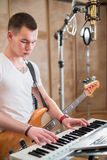 Musician with a guitar around his neck plays keyboard stock images
