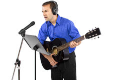 Musician with Guitar. Male singer holding a guitar and wearing headphones on white background Royalty Free Stock Images