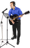 Musician with Guitar. Male singer holding a guitar and wearing headphones on white background Royalty Free Stock Image