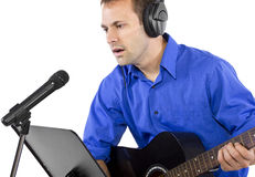 Musician with Guitar. Male singer holding a guitar and wearing headphones on white background Royalty Free Stock Photography