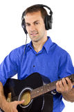 Musician with Guitar. Male singer holding a guitar and wearing headphones on white background Stock Photos