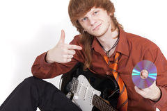 Musician with guitar selling compact disc Stock Photography