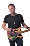 Musician with guitar. Young musician with an attractive alternative rock style keeps his guitar in his hands and laughs. On a white background, studio shot stock image