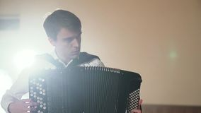 Musician hand playing accordion closeup in stage lights shadows. FullHD stock video