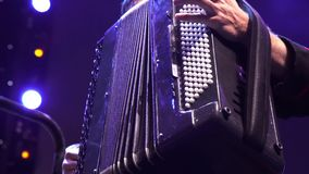 Musician hand playing accordion closeup in stage lights shadows stock video footage