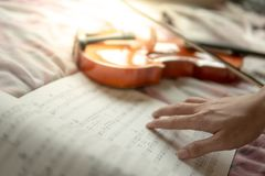 Musician hand on sheet of music note ans violin. Musician hand on sheet of music note and vintage violin on flowery pink bed in the bedroom. Playing music stock photography