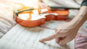 Musician hand on sheet of music note ans violin. Musician hand pointing on sheet of music note and vintage violin on flowery pink bed in the bedroom. Playing royalty free stock photography