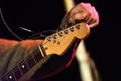 Musicians hand is tuning an electric guitar on the stage. Musician hand is tuning the strings at the headstock of an electric guitar on stage, selected focus Royalty Free Stock Photo
