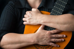 Musician hands embracing a classic acoustic guitar Stock Images