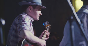 Musician in hat plays guitar in night club, close up. Telephoto Royalty Free Stock Image