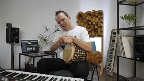 Musician having wrist pain while playing djembe drum instrument in home music studio. Professional musician having wrist pain while playing djembe music stock video footage