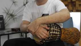 Musician having wrist pain while playing djembe drum instrument in home music studio. Professional musician having wrist pain while playing djembe music stock video
