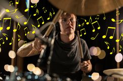 Musician in headphones playing drum kit at concert Stock Photo