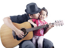Musician with his daughter. Shot of a musician kissing his daughter shot in studio on white Royalty Free Stock Images